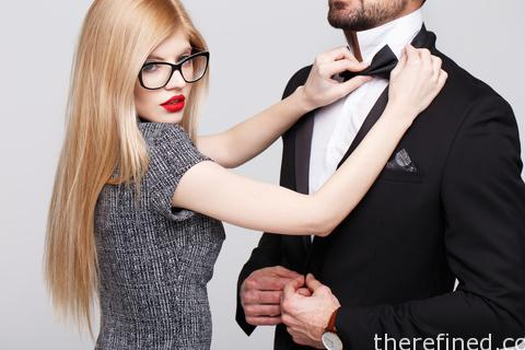 Young blonde woman tying bow tie for stylish man